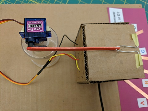 Using a piece of wire, attach the end of the popsicle stick to the box lid