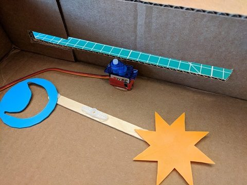 Sun and moon attached to either ends of a popsicle stick with servo arm in the center