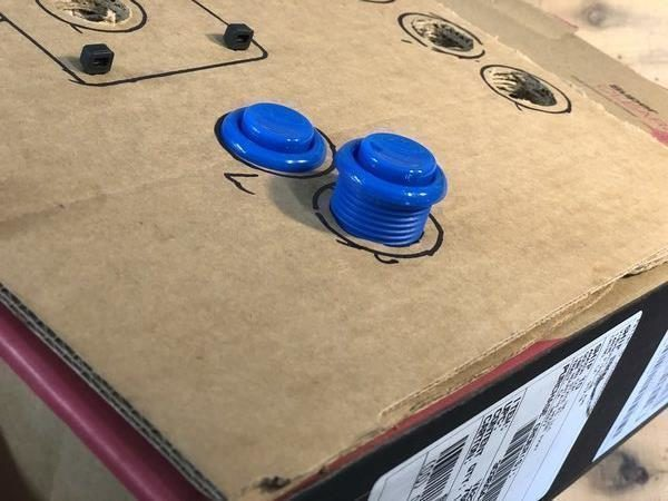 Two buttons squeezed into cardboard holes