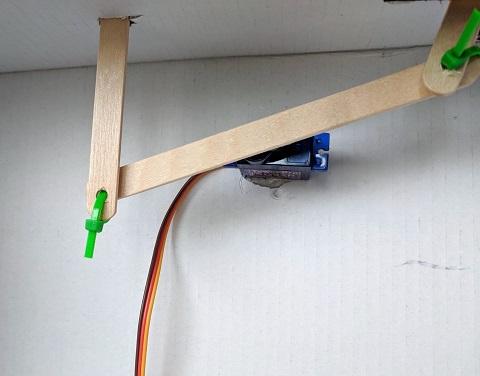 Attach two vertical rocker arm popsicle sticks