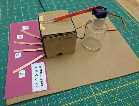 Build a servo stand behind the box and position servo arm and popsicle stick