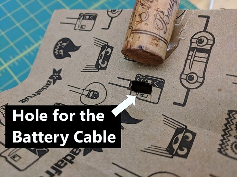A hole cut for the battery cable below the cork
