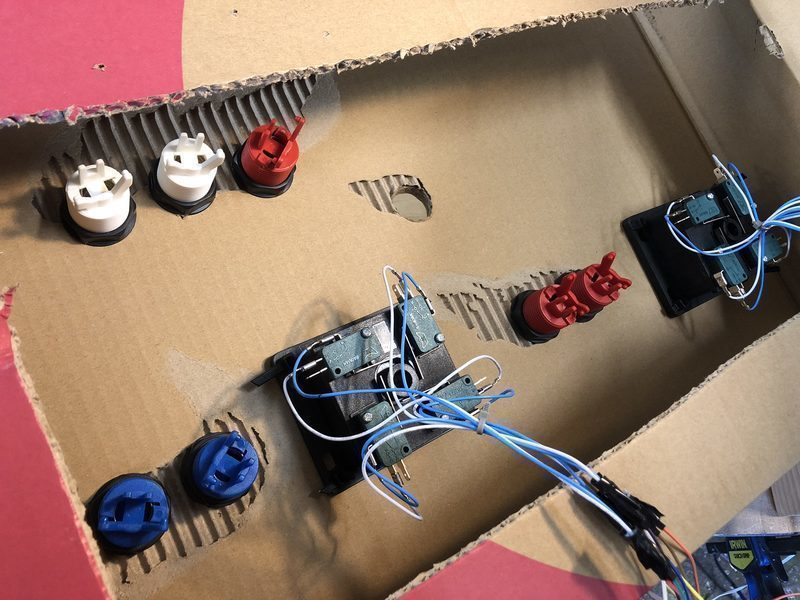 Buttons and joysticks inserted into the cardboard box