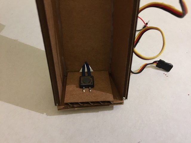 Glue the pushbutton to the bottom of the chute