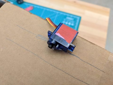 Line up a continuous motion servo motor against the wall of a box
